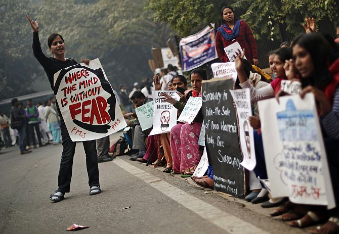 Protesters carry placards as they shout slogans during a protest to mark the first anniversary of the Delhi gang rape