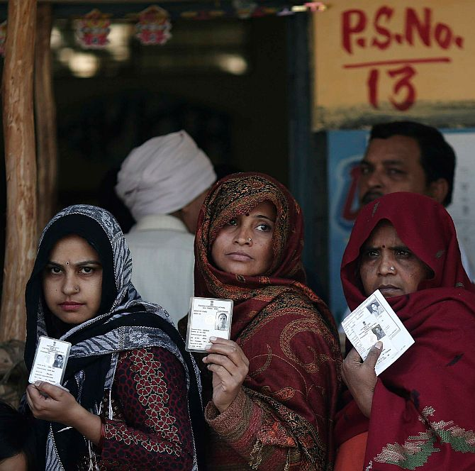Voters queue inside a polling station to cast their vote during the Delhi assembly election.