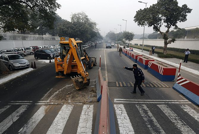 A traffic policeman guides a bulldozer removing the security barriers in front of the US embassy in New Delhi
