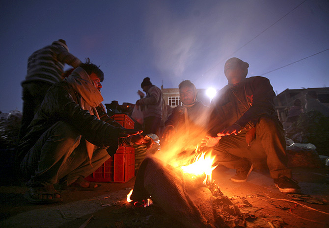 People warm themselves around a fire at a vegetable wholesale market in Jammu.