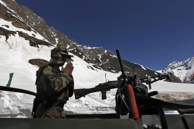 An Indian army soldier prays before leading a convoy of trucks through a mountainous road after the Srinagar-Leh highway was opened to traffic in Zojila 108 km east of Srinagar
