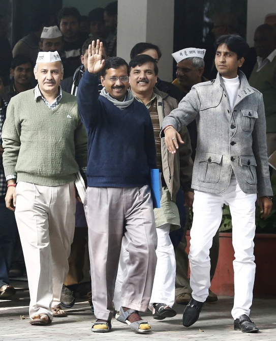 Arvind Kejriwal (centre), leader of the newly formed Aam Aadmi Party, waves after his meeting with the Delhi's Lieutenant Governor Najeeb Jung in New Delhi