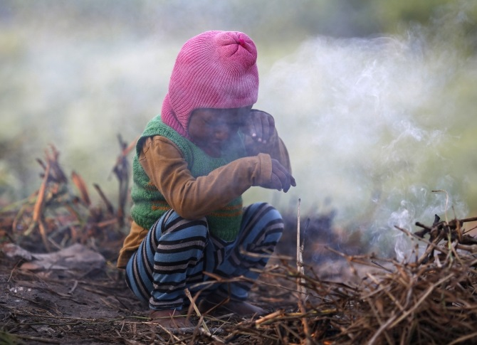 A boy wipes his eye as he sits near twigs which were set on fire by his parents to warm themselves at a vegetable field