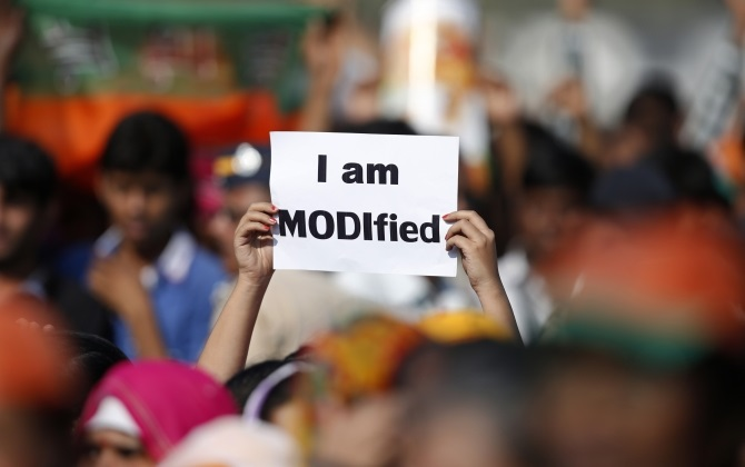 A supporter of Narendra Modi holds a placard during a rally