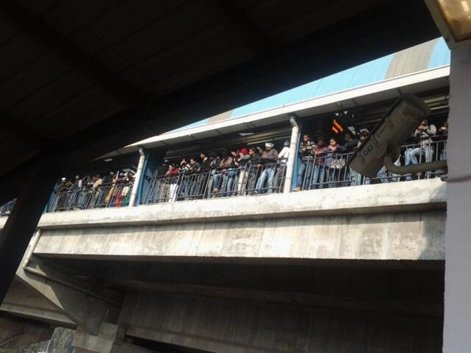 Crowds gather at a metro station in Delhi to get a glimpse of Kejriwal