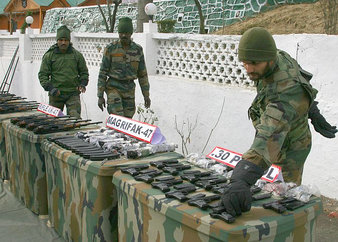 Army troopers showcase the seized weapons, in Srinagar on Sunday