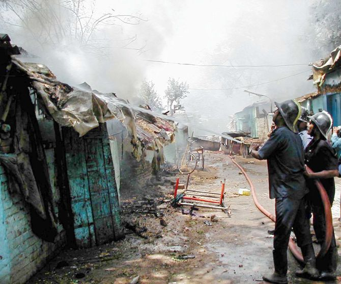 Firemen fights a blaze in a riot-hit neighbourhood of Ahmedabad in 2002