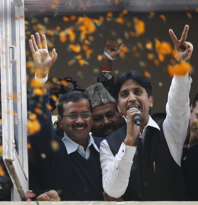 Delhi CM Arvind Kejriwal waves to the crwods as AAP leader Kumar Vishwas shows the victory sign in New Delhi