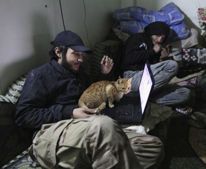 A Free Syrian Army fighter works on his computer in Deir al-Zor.