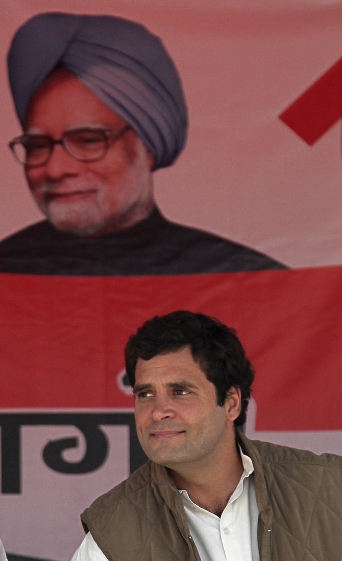 Rahul Gandhi sits under a poster of Prime Minister Manmohan Singh at a rally in Uttar Pradesh