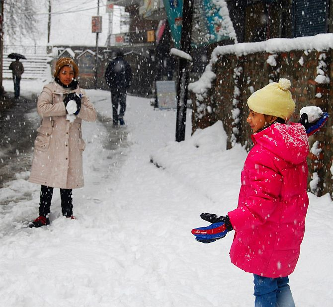 Tourists play in snow in Srinagar on Tuesday