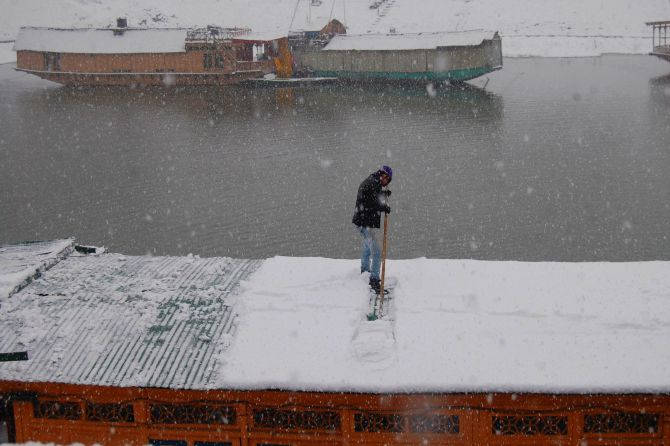 A man clears snow on the roof of a houseboat on Dal Lake on Tuesday