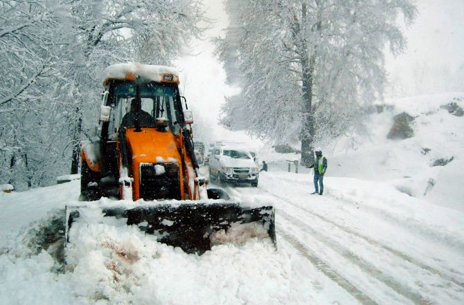 A snow cutting machine clears snow on the Jammu Srinagar highway on Tuesday