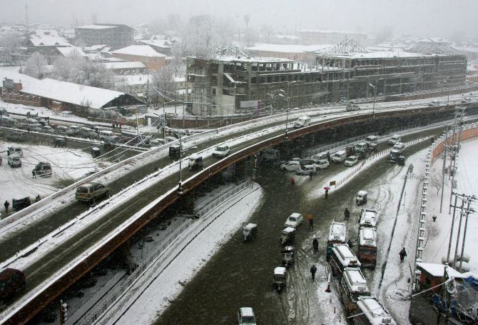 Vehicles move sluggishly during heavy snowfall in Srinagar on Tuesday