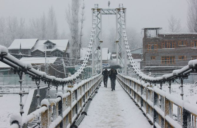 People walk on a snow covered bridge during heavy snowfall in Srinagar on Tuesday