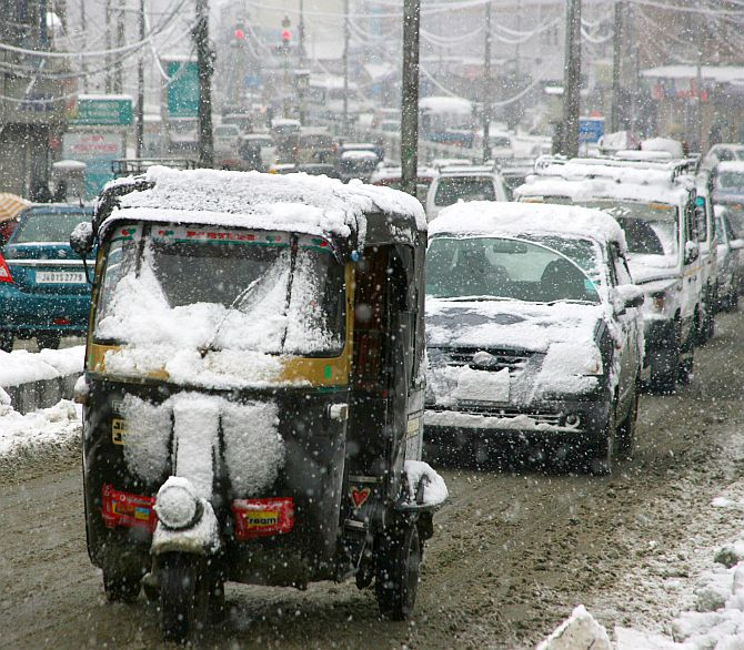 Vehicles move slowly during heavy snowfall in Srinagar on Tuesday