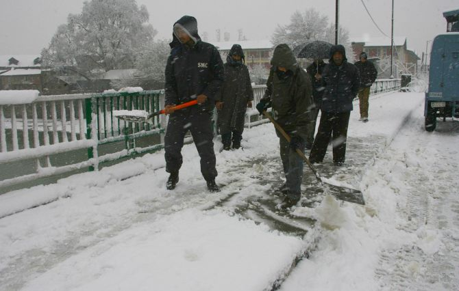 Srinagar Municipal Corporation workers clear snow on the roads on Tuesday