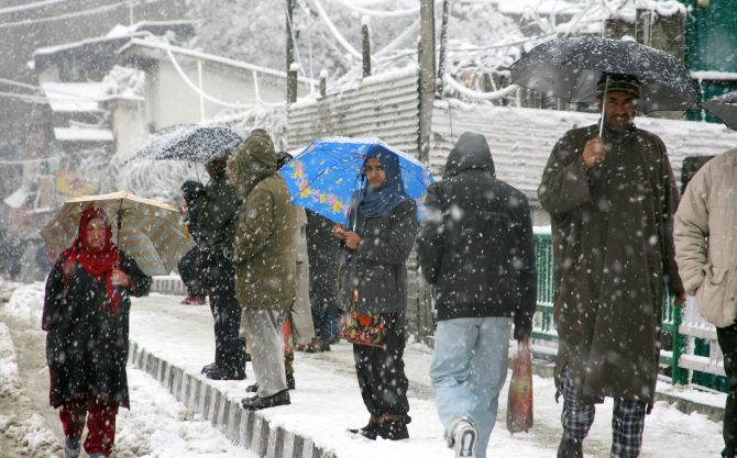 People walk during heavy snowfall in Srinagar on Tuesday