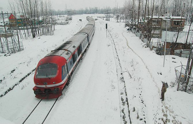 A train moves on snow-covered tracks during heavy snowfall in Kashmir on Tuesday