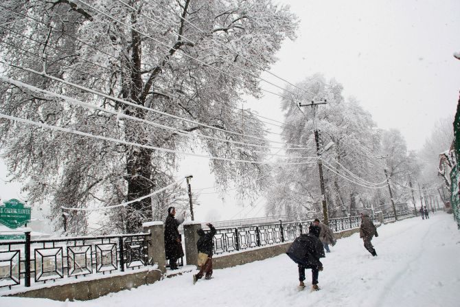 Children play in the snow during heavy snowfall in Srinagar on Tuesday