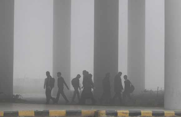 Airport staff walk towards the main terminal amid heavy fog in New Delhi