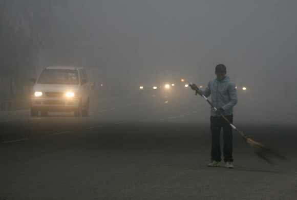 A sweeper cleans a busy road on a cold and foggy morning in New Delhi