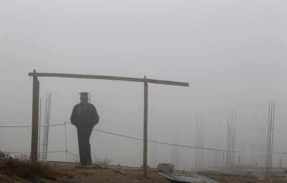 A security staff stands guard at a construction site in New Delhi