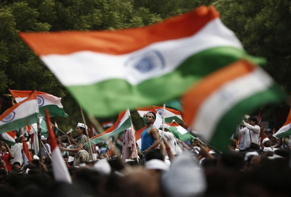 Supporters of Anna Hazare wave the national flag as they protest for a stronger Lokpal, in New Delhi