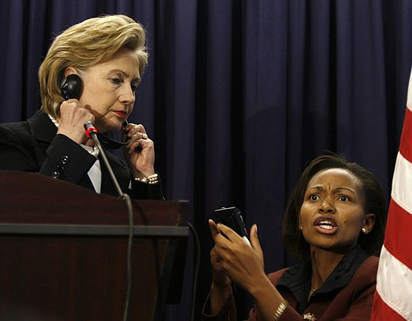 Hillary Clinton is assisted by a technician in adjusting her translation device during a news conference at the US embassy in Kenya's capital Nairobi