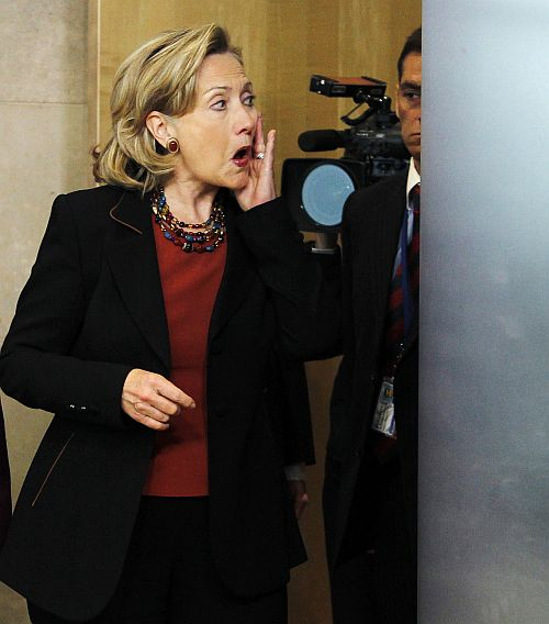 Hillary Clinton adjusts her make-up before a news conference at the EU Commission headquarters in Brussels