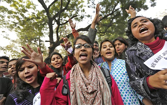Demonstrators shout slogans and raise their hands during a protest against the Delhi gang rape
