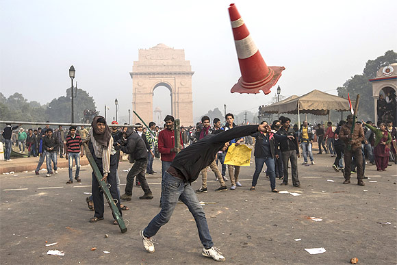 Protestors throw projectiles at Delhi police officers during a protest against the Indian governments reaction to recent rape incidents