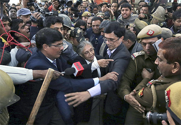 -Delhi's Chief Minister Sheila Dixit (C) is escorted by security personnel after she was blocked by demonstrators while entering the venue for the protests in New Delhi