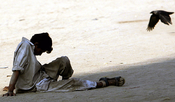 An unemployed migrant worker sits on a ground in Mumbai