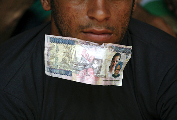 A fake currency note, with images of Prime Minister Manmohan Singh and Congress chief Sonia Gandhi, is worn by a protestor in New Delhi