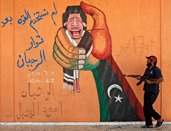 File photo of a Libyan rebel fighter walking past a graffiti depicting Muammar Gaddafi at a checkpoint near Yafran in western Libya