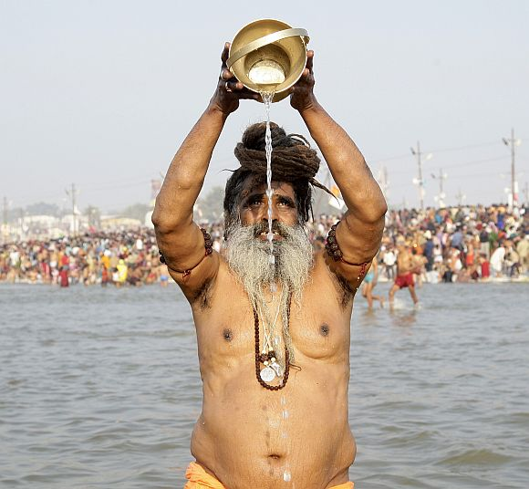 A sadhu prays after taking dip in the waters of the Ganga