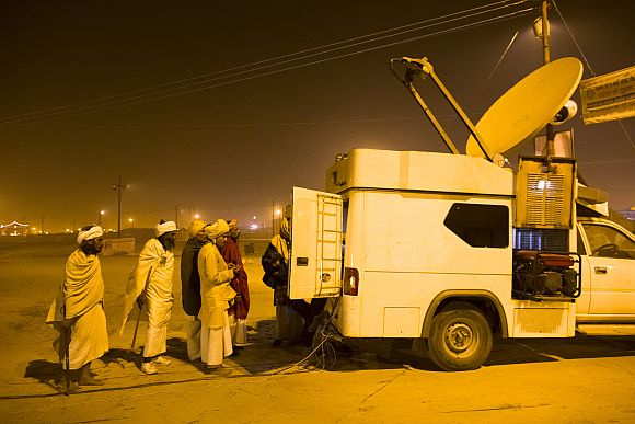 Hindu devotees line up to see the ongoings inside of a TV satelite truck parked on the banks of the Ganga