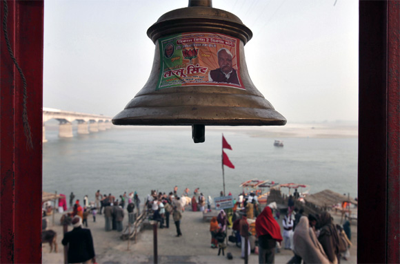 A temple bell pasted with a pamphlet of BJP is seen on the banks of the river Saryu in Ayodhya