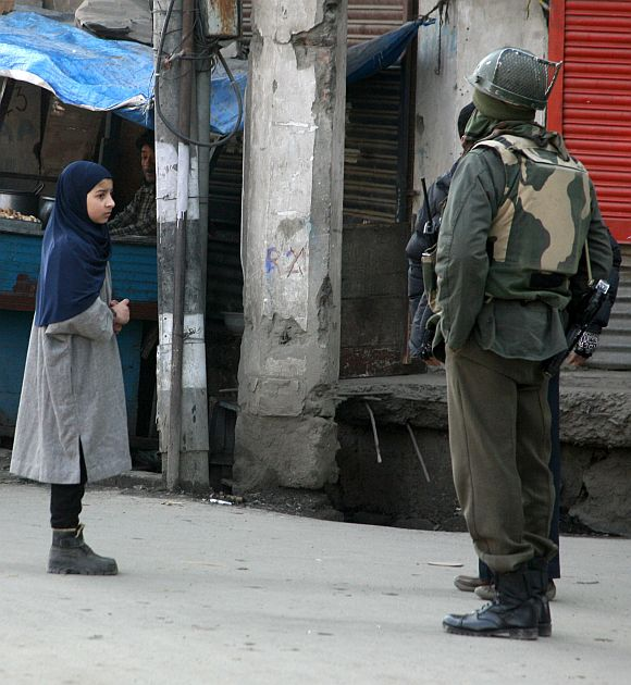 A Kashmiri girl seeks permission from security personal to access a cordoned off street