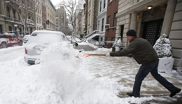 A man shovels snow from the sidewalk on the Upper East Side of New York