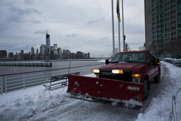 A truck with a snow plough cleans along the Hudson river as the skyline of New York's Lower Manhattan and One World Trade Center is seen at Newport in New Jersey