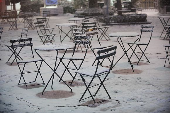 Snow covers cafe tables and chairs in New York's Bryan Park