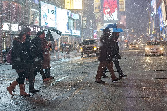People make their way through snow in New York's Times Square