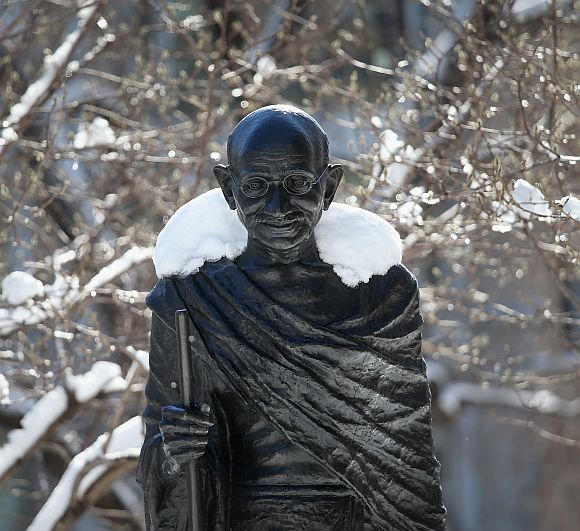 Snow blankets the shoulders of a statue of Mahatma Gandhi in Union Sqaure, New York
