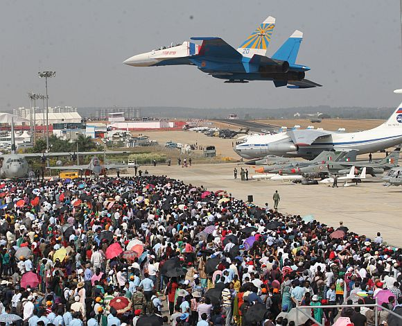 A jet, part of the Russian Knights aerobatic team, wows the audience at the Aero India 2013 in Bengaluru
