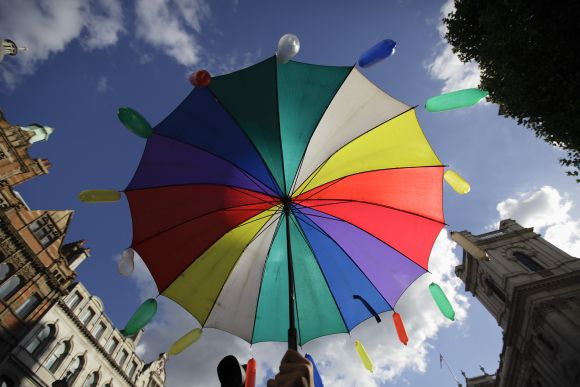 A protester holds an umbrella with coloured condoms during a demonstration against the Pope's visit in London