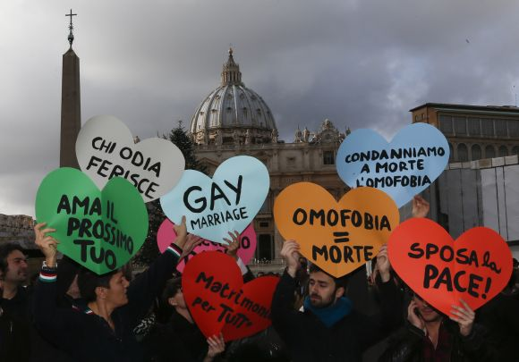 Members of a gay activist group hold signs in front of St. Peter's square in the Vatican on December 16, 2012.