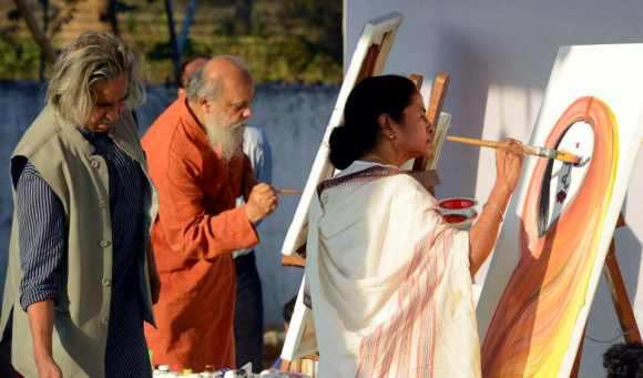 Mamata Banerjee paints during the Maati Utsav in Kolkata