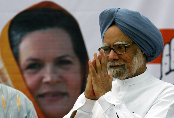 Prime Minister Manmohan Singh in front of a poster of UPA chairperson Sonia Gandhi
